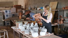 Two cheerful artisans having ceramics. In hands and standing in workshop stock video footage
