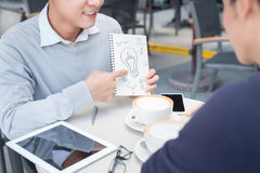 Two cheerful asian business people discussing with documents Stock Photography