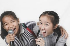 Two cheerful asian teenager singing with microphone isolated white background royalty free stock photos