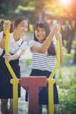 Two cheerful asian teenager toothy smiling face in public playground stock photography