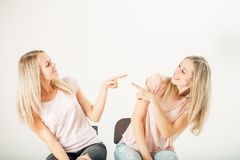 Two attrative sisters twins pointing over white background. Two cheerful attrative sisters twins pointing over white background Stock Photo