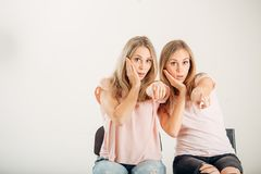 Two attrative sisters twins pointing over white background. Two cheerful attrative sisters twins pointing over white background Royalty Free Stock Photo