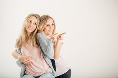 Two cheerful attrative sisters twins pointing over white background.  Royalty Free Stock Photography