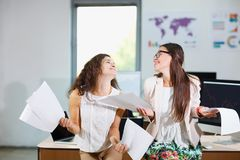 Two cheerful beautiful young business girls in the office. Close-up of two cheerful young business girls in white blouses holding documents Royalty Free Stock Image