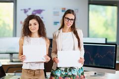Two cheerful beautiful young business girls in the office. Close-up of two cheerful young business girls in white blouses holding documents Stock Photos