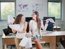 Two cheerful beautiful young business girls in the office. Close-up of two cheerful young business girls in white blouses holding documents Royalty Free Stock Photo