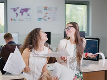 Two cheerful beautiful young business girls in the office. Close-up of two cheerful young business girls in white blouses holding documents Royalty Free Stock Photos