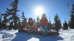 Two cheerful beautiful young girls snowboarders or skiers enjoy sitting in a snowdrift and throwing snow, smiling. Women