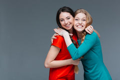 Two cheerful beautiful young women standing and hugging Royalty Free Stock Images