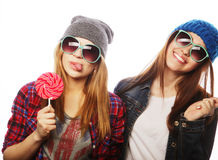 Two cheerful best friends. Portrait of two young pretty hipster girls wearing hats and sunglasses holding candys. Studio portrait of two cheerful best friends stock images