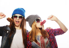 Two cheerful best friends. Portrait of two young pretty hipster girls wearing hats and sunglasses holding candys. Studio portrait of two cheerful best friends royalty free stock photos