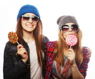 Two cheerful best friends. Portrait of two young pretty hipster girls wearing hats and sunglasses holding candys. Studio portrait of two cheerful best friends stock photos