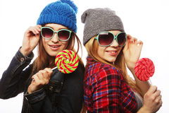 Two cheerful best friends. Portrait of two young pretty hipster girls wearing hats and sunglasses holding candys. Studio portrait of two cheerful best friends stock photo