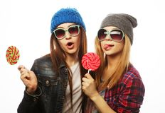 Two cheerful best friends. Portrait of two young pretty hipster girls wearing hats and sunglasses holding candys. Studio portrait of two cheerful best friends stock image