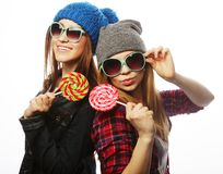 Two cheerful best friends. Portrait of two young pretty hipster girls wearing hats and sunglasses holding candys. Studio portrait of two cheerful best friends royalty free stock photo