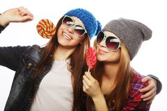 Two cheerful best friends. Portrait of two young pretty hipster girls wearing hats and sunglasses holding candys. Studio portrait of two cheerful best friends royalty free stock image