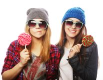 Two cheerful best friends. Portrait of two young pretty hipster girls wearing hats and sunglasses holding candys. Studio portrait of two cheerful best friends royalty free stock images