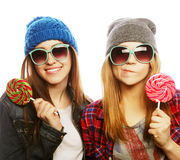 Two cheerful best friends. Portrait of two young pretty hipster girls wearing hats and sunglasses holding candys. Studio portrait of two cheerful best friends stock photography