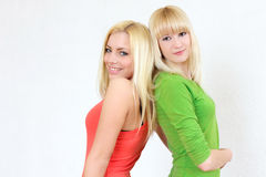 Two cheerful blonde girl with long hair in pink an Stock Image