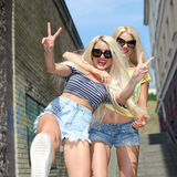Two cheerful blondes. Having fun on the background of the transition to the metro Stock Image