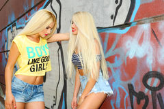 Two cheerful blondes. Having fun on the background of the transition to the metro Royalty Free Stock Images