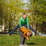 Two cheerful boys play outdoors, jump the friend through the fri Royalty Free Stock Images
