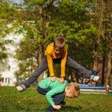 Two cheerful boys play outdoors, jump the friend through the fri Stock Photos