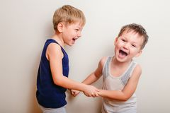 Two cheerful boys play together and scream. Two cheerful little boys play together, hold hands and scream stock photo