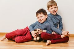 Two cheerful brother sitting next to each other to the floor stock photo
