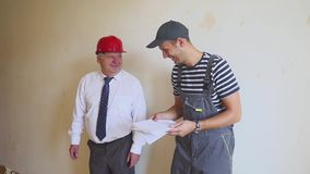 Two cheerful builders are discussing the construction plan and laughing. Senior engineer and young worker discuss the stock video