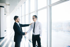 Two cheerful business men shaking hands and smiling in the background stock photography
