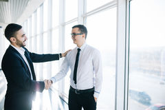 Two cheerful business men shaking hands and smiling stock photo