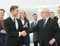 Two cheerful business people shaking hands while their colleague Royalty Free Stock Images