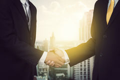Two cheerful businessman shaking hands with city background Royalty Free Stock Photos
