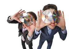 Two cheerful businessmen offering DVDs on sale Stock Images
