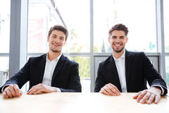 Two cheerful businessmen sitting at the table in office Royalty Free Stock Photos