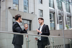 Two cheerful businessmen using tablet and drinking coffee Royalty Free Stock Photos