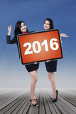Two cheerful businesswomen hold numbers 2016 Royalty Free Stock Photo