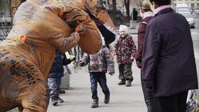 Two cheerful kids playing with person in dinosaur costume at sidewalk. Two cheerful caucasian kids playing with person in dinosaur costume at sidewalk. Cold stock footage
