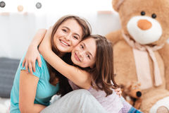 Two cheerful charming sisters embracing at home Stock Images
