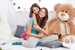 Two cheerful charming sisters sitting in children room Royalty Free Stock Photography
