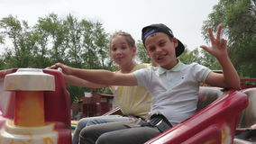 Two cheerful child prepare for a trip to the attraction, waving their hands and laughing. A boy and girl are rideing on the carousel in an amusement park stock video footage