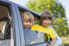 Two cheerful child sitting in the car Royalty Free Stock Image