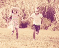Two cheerful children active playing and running outdoors Stock Photos