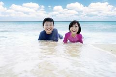 Two cheerful children playing waves on beach. Picture of two cheerful children looking at the camera while playing waves on the tropical beach Royalty Free Stock Photography