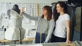 Two cheerful clothing designers are making funny selfie with smart phone while standing beside clothed mannequin in. Two cheerful female clothing designers are stock video