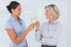 Two cheerful colleagues clinking their flutes of champagne Stock Photos
