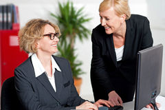 Two cheerful corporate women in office Royalty Free Stock Photography