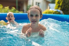 Two cheerful cute little sisters playing and having fun, splashing and jumping in inflatable pool at backyard.  royalty free stock image