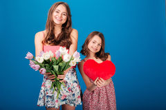 Two cheerful cute sisters holding bouquet of flowers and heart Stock Photos